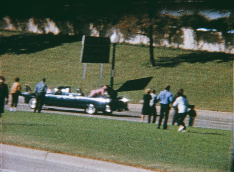 Bystanders look on as Jacqueline Kennedy reaches over to help husband John F. Kennedy who lies on the rear of a car after being struck by an assassin's bullet
