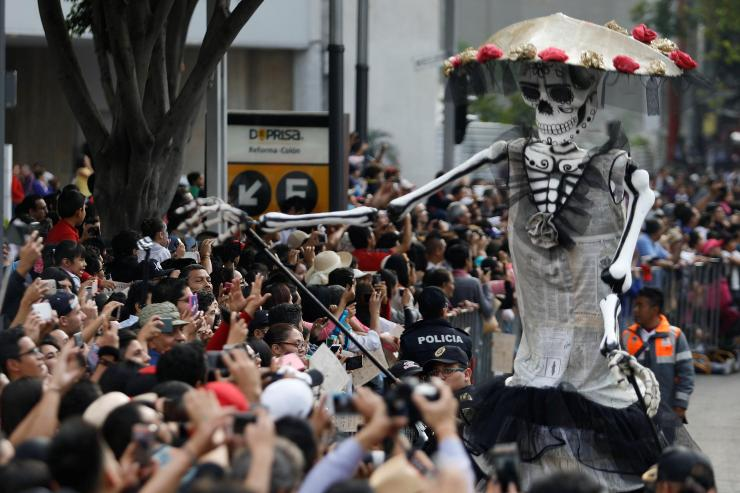Walking skeletons in the parade reached out to greet the crowds of people who had come to celebrate