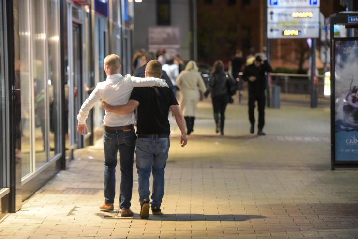 Two mates help each other down the road on Saturday night