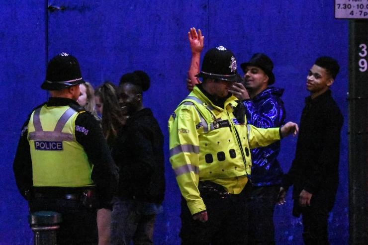 Police chat to people partying on the street to celebrate October 31 on the night of October 28