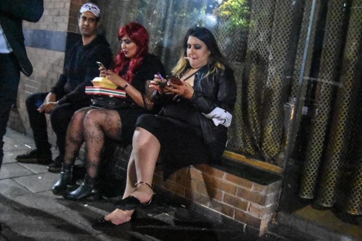 Two women take a break, checking their phones, as they celebrate the night