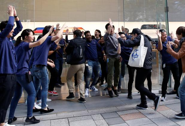 Working staff cheer for the first one who buy the newly released iPhone X at the Sanlitun Apple Store in Beijing