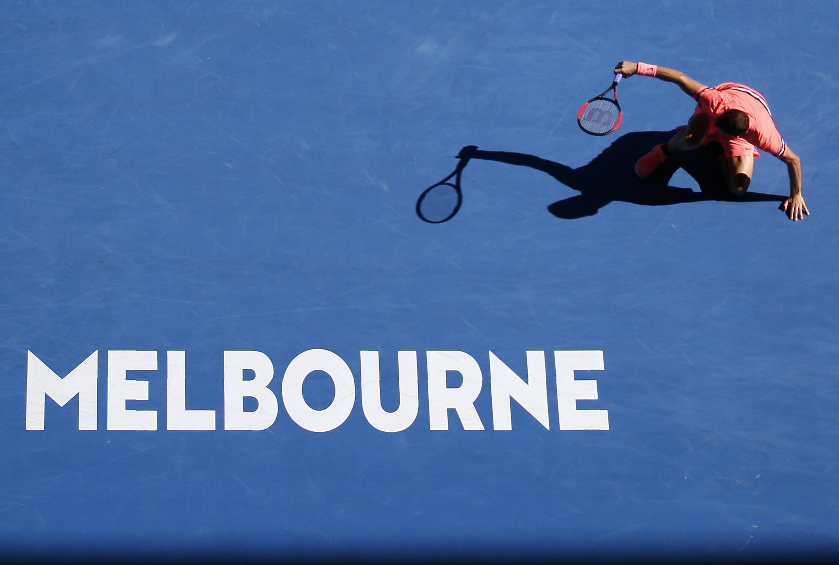 Grigor Dimitrov falls to the ground at Rod Laver Arena