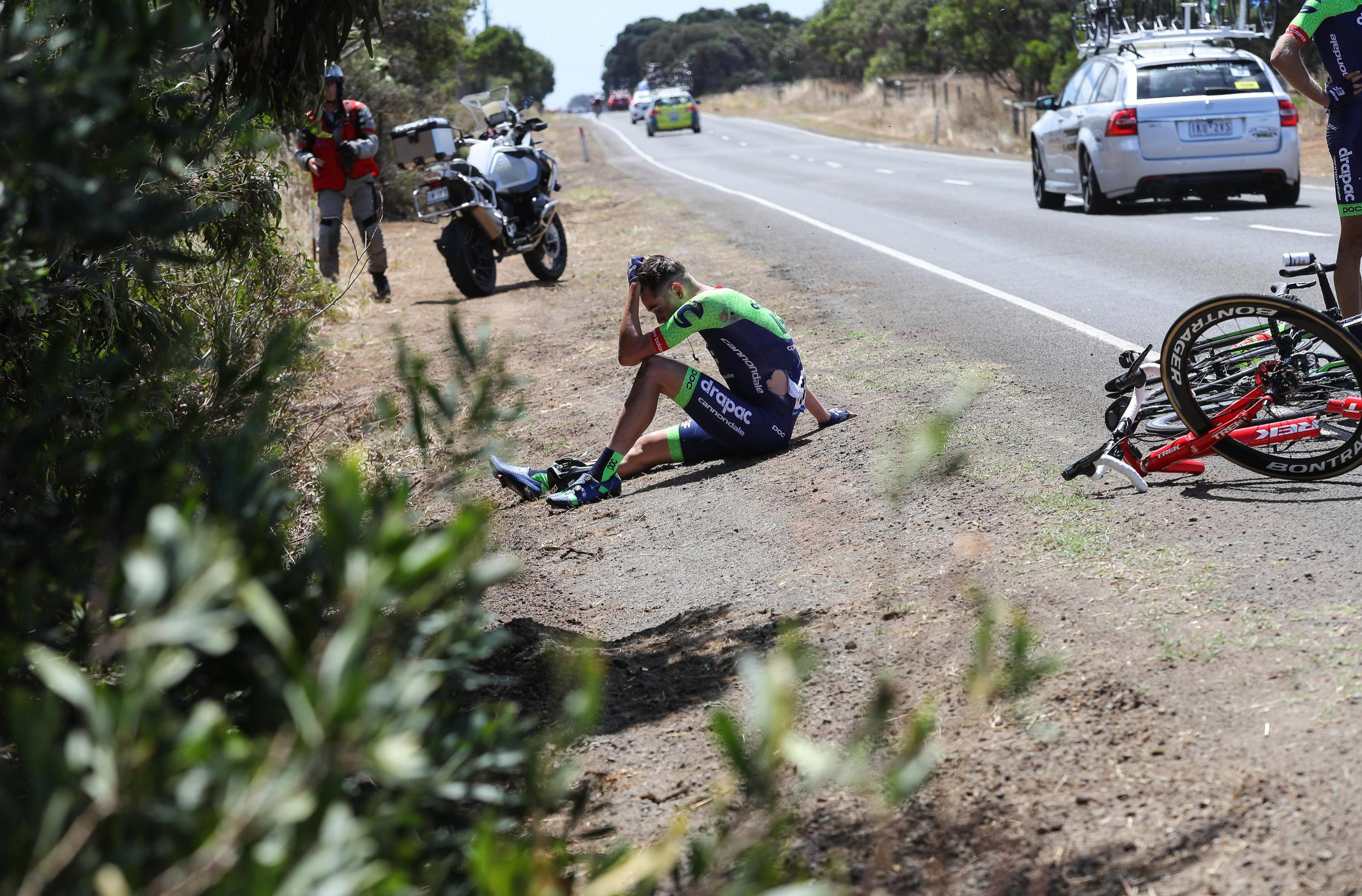 Drapac EF rider Thomas Kaesler sat down on the ground looking dazed and without a helmet after the ugly crash in Victoria