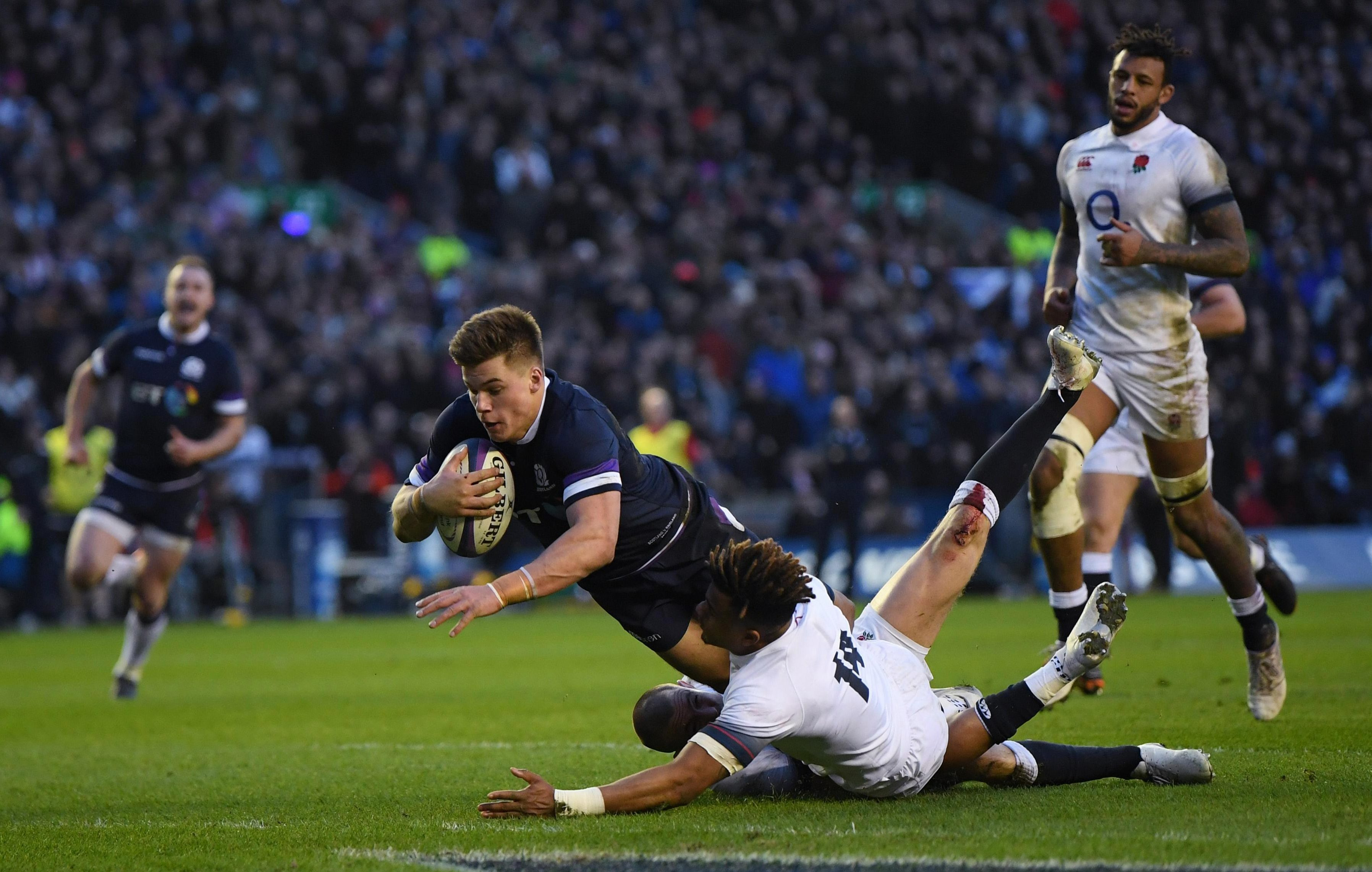 Huw Jones scores Scotland's third try despite the best efforts of England's Anthony Watson
