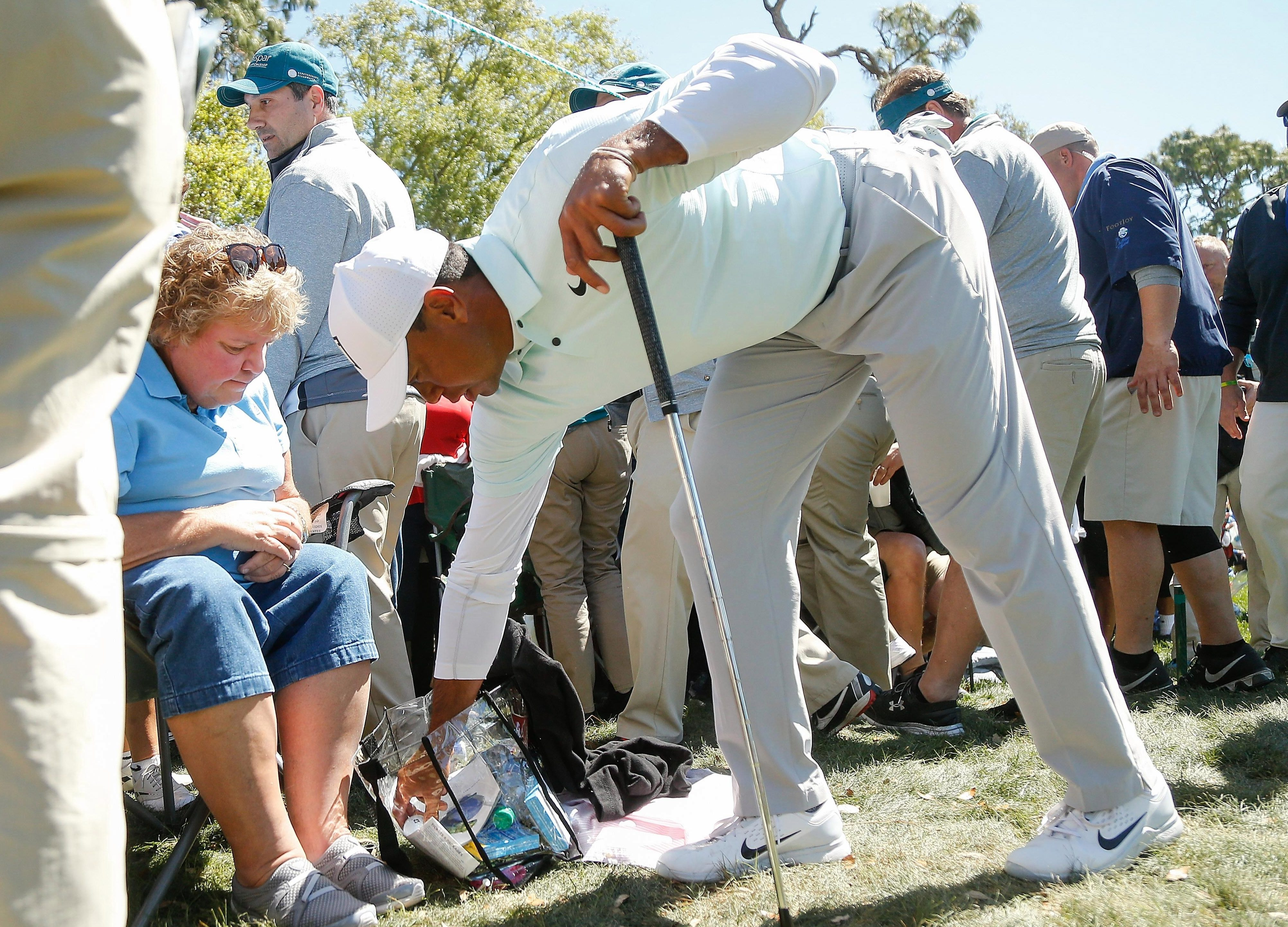 The female spectator did not move as Tiger Woods picked his ball out of her hold-all