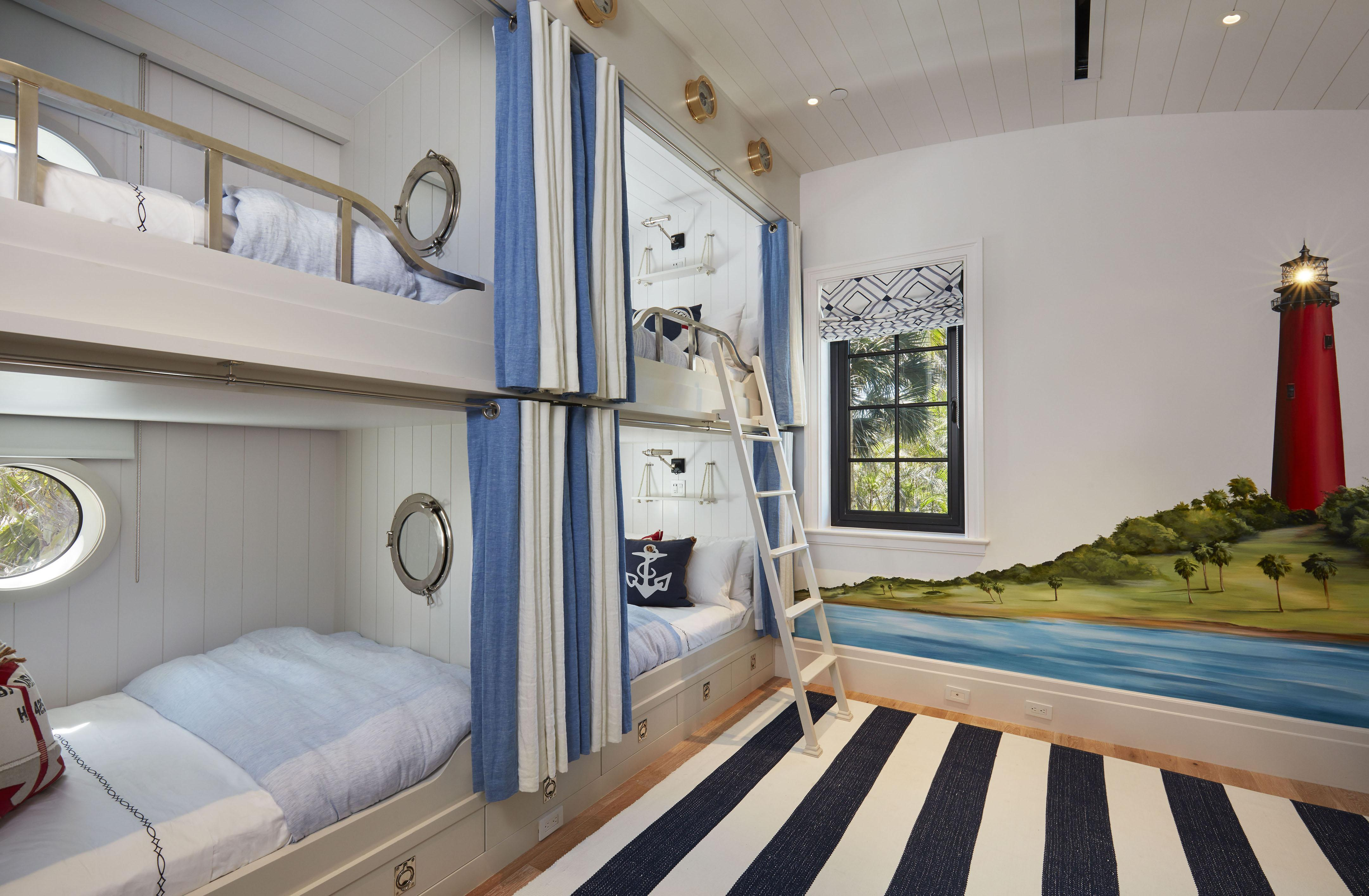 Two bunk beds are placed side-by-side in one bedroom with a lighthouse painting on the wall