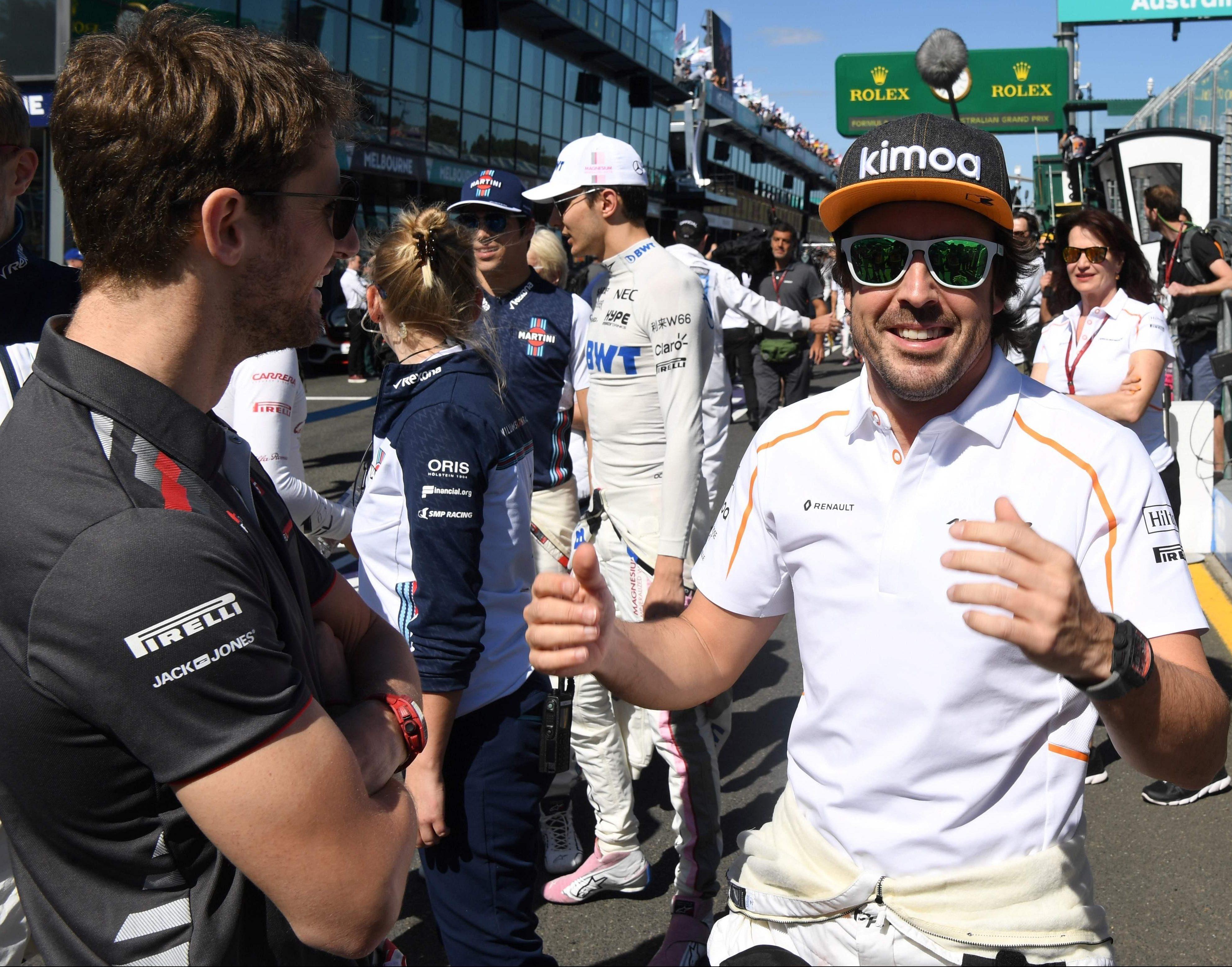 Grosjean chats to Fernando Alonso, who has labelled the 2018 Haas car a 'Ferrari replica'
