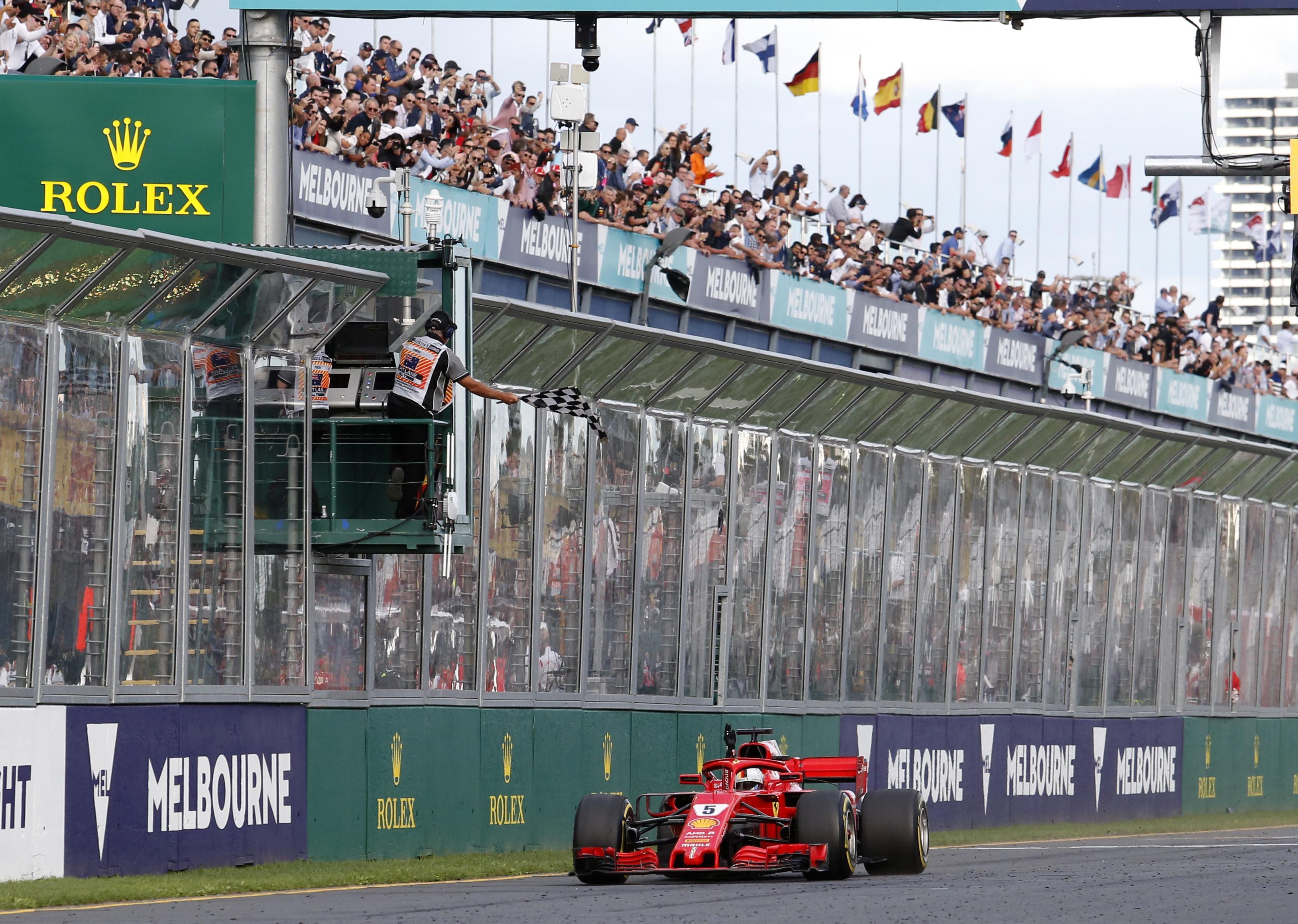 Sebastian Vettel crosses the finish line just ahead of Lewis Hamiltoin in Melbourne