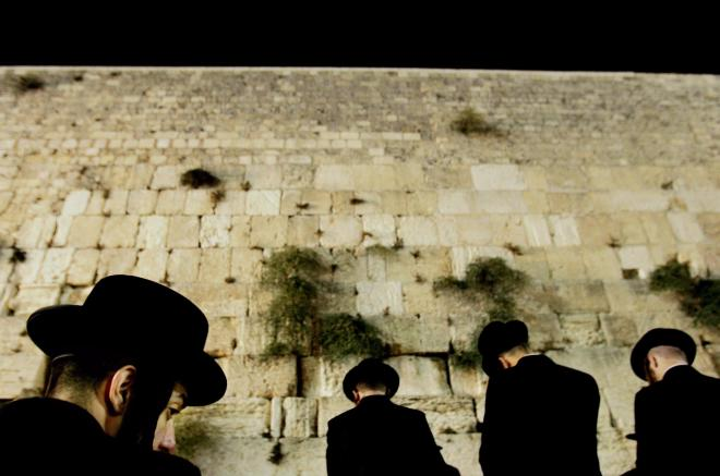 Ultra-orthodox Jewish men pray at the floodlit Western Wall, Judaism's holiest site, before the holiday of Yom Kippur, in Jerusalem