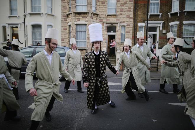 A group of Orthodox Jewish boys dance in the street before going to collect money for their school during Purim
