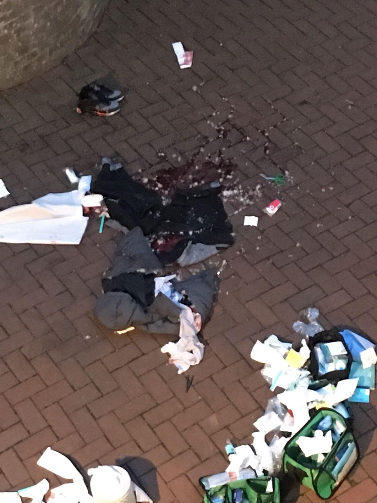 Blood and clothes pictured at the scene in Ealing Broadway where a man in his late teens was stabbed