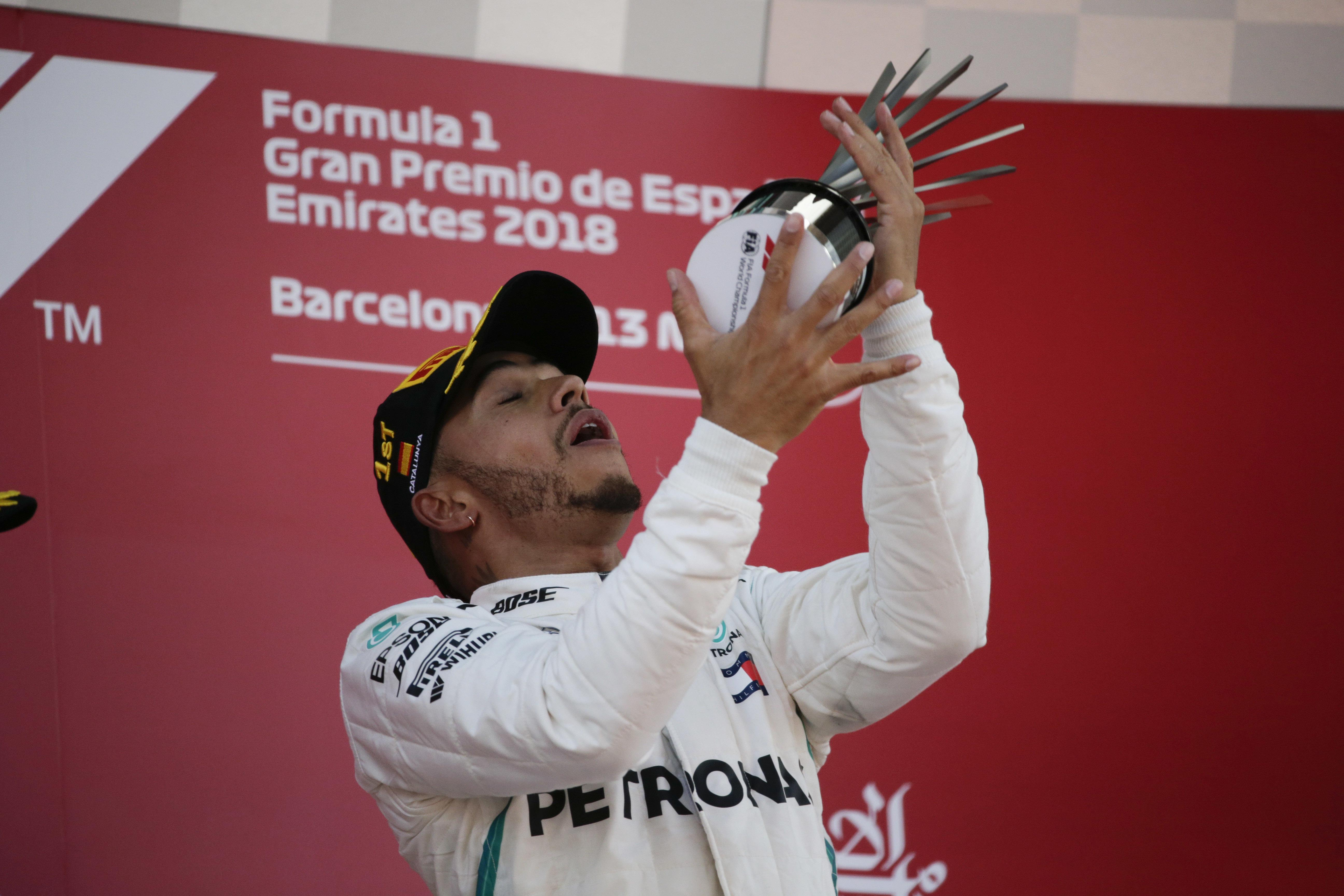Lewis Hamilton gets to grips with his trophy after winning the Spanish GP in style