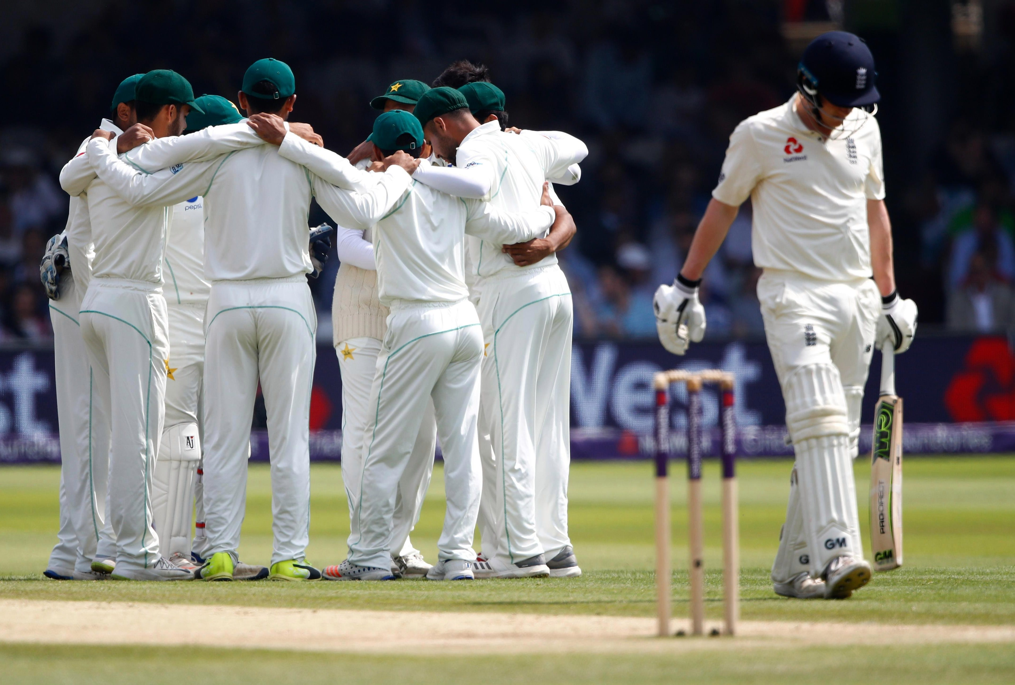 Pakistan link up for a huddle as Dom Bess makes his way back to the changing room after he was bowled