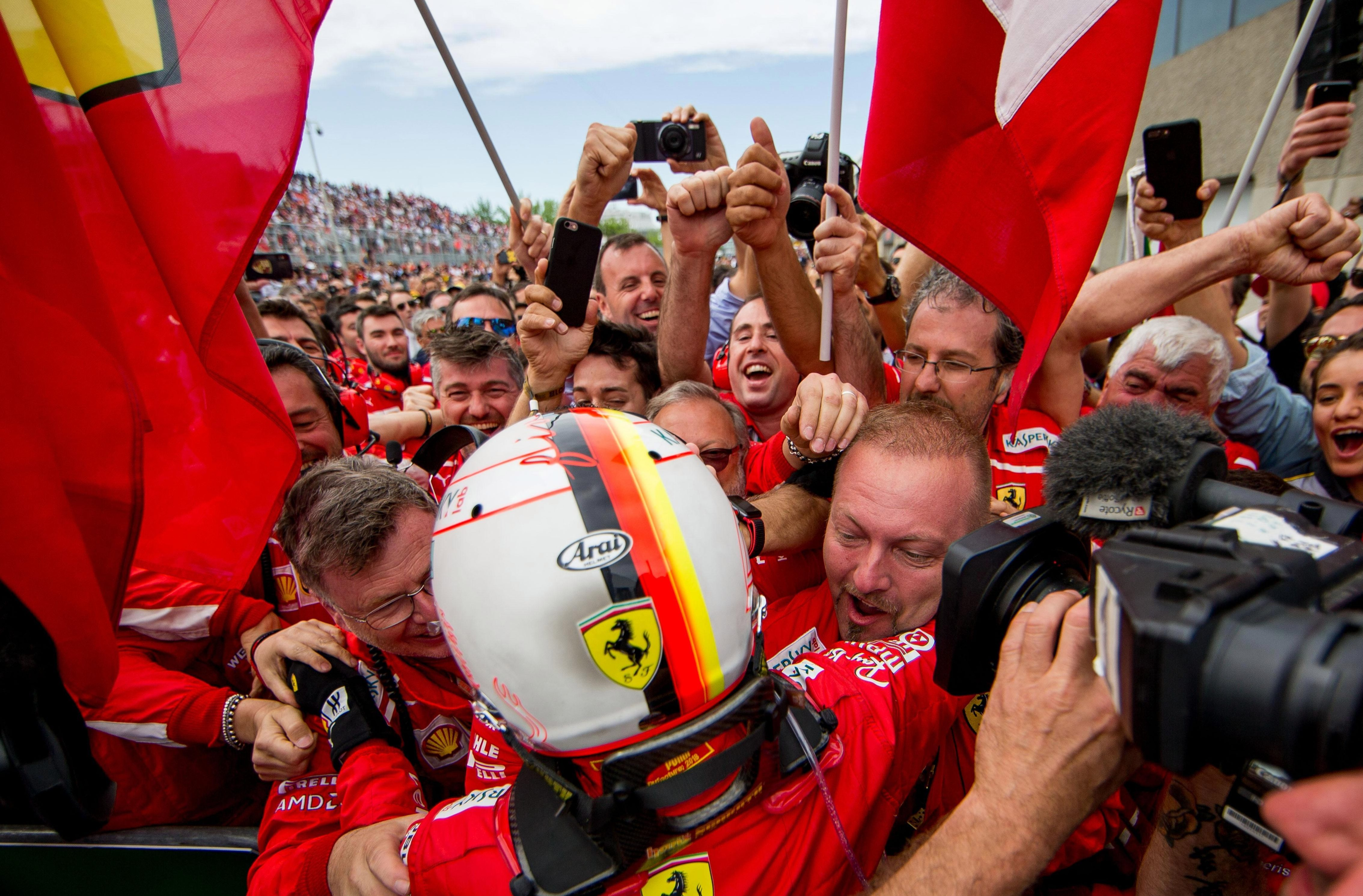 Seb Vettel is mobbed by his Ferrari team-mates