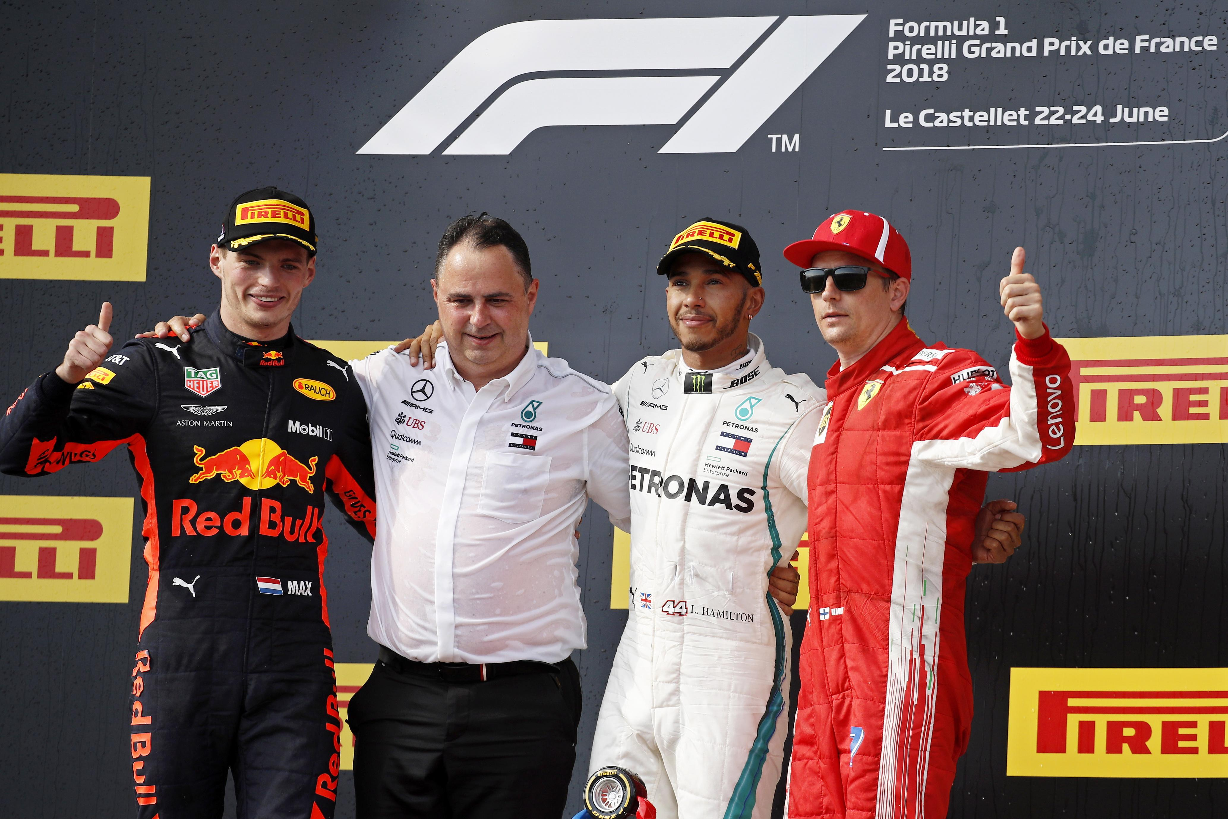 Lewis Hamilton celebrates on the podium next to team manager Ron Meadows, Max Verstappen and Kimi Raikkonen.
