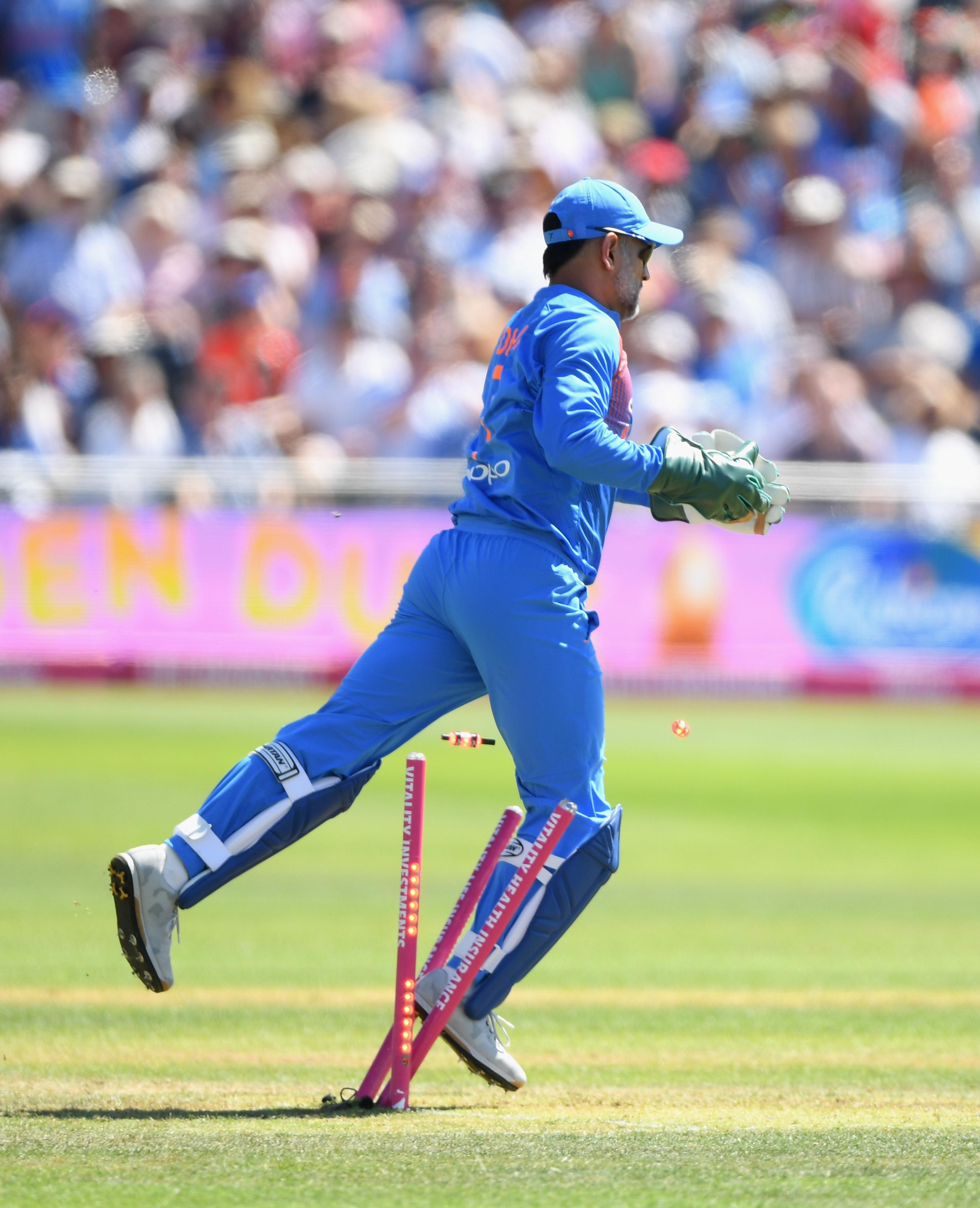 MS Dhoni collides with the stumps after taking a catch to dismiss Eoin Morgan