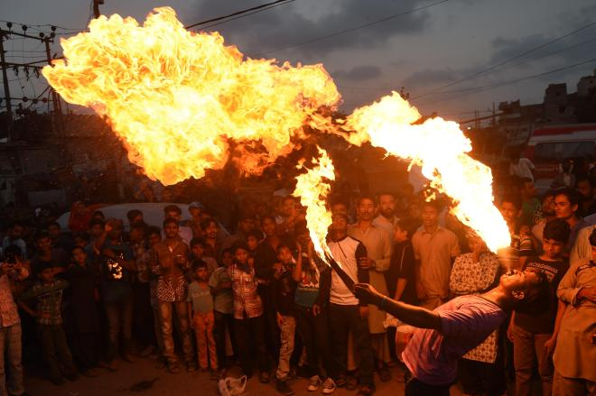 A Pakistani Sunni Muslim spits fire during an Ashura procession in Karachi