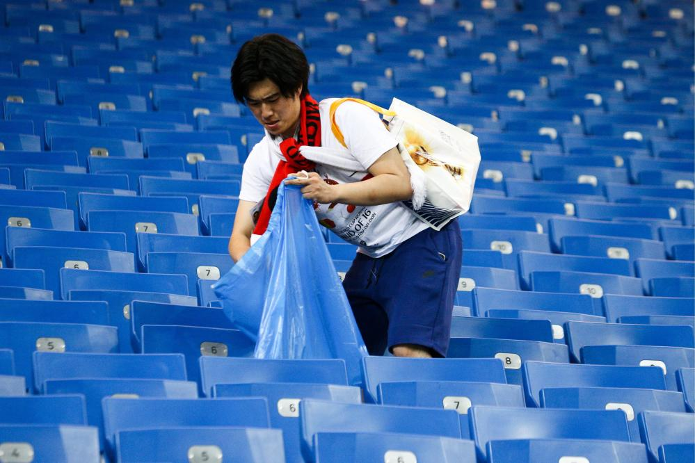 Japan supporters stayed behind to clear the stadium after defeat to Belgium