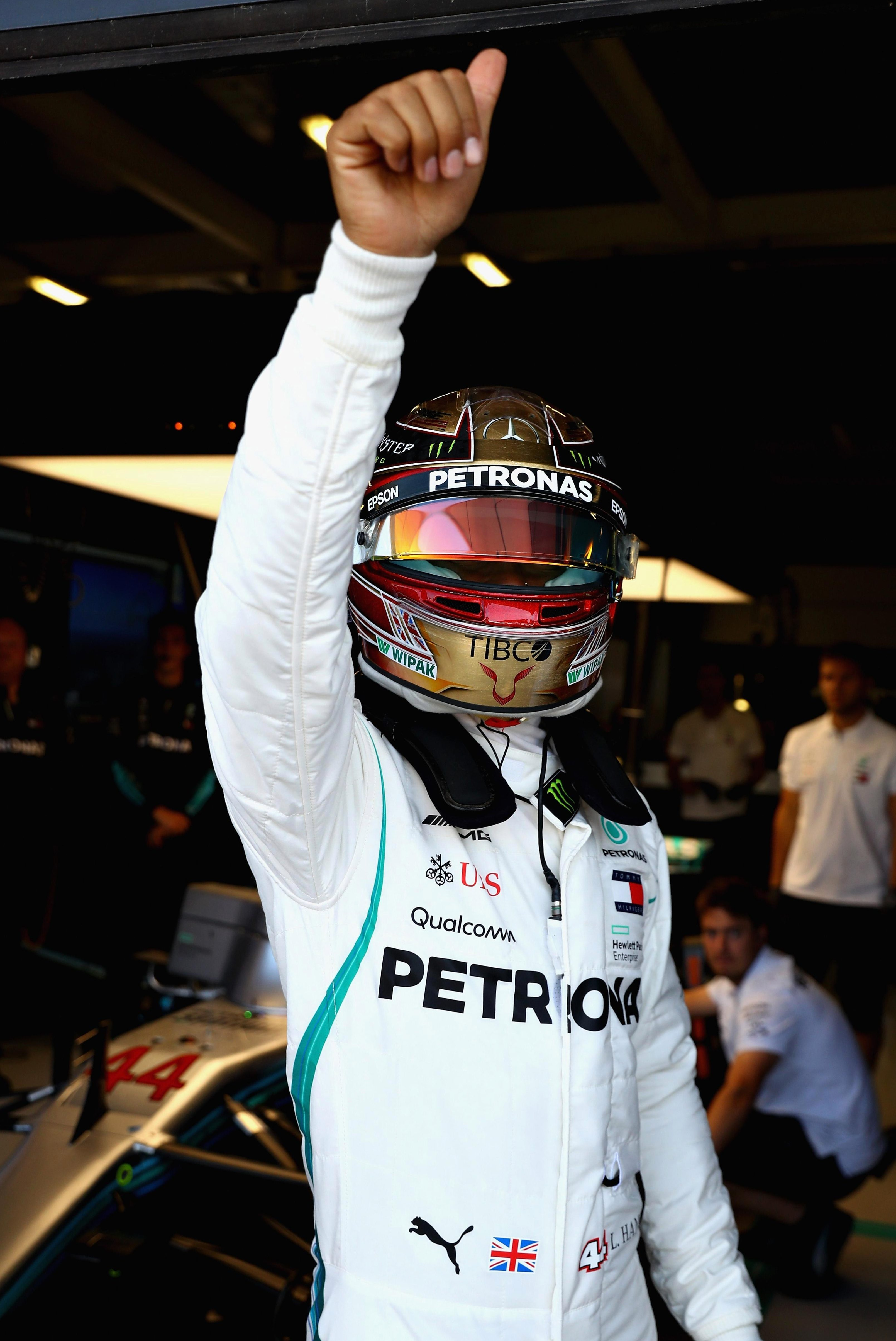 Lewis Hamilton waves to his home support as he secured a place on the front of the grid for the British GP