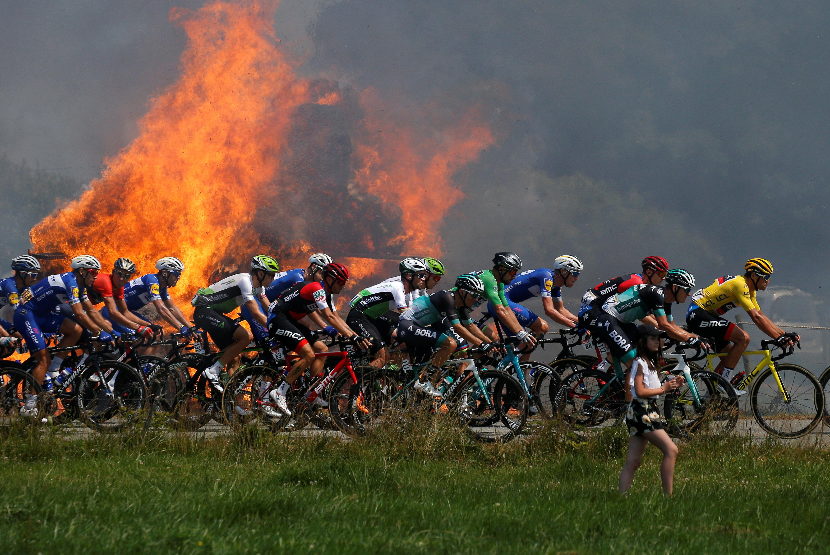The peloton roared past but luckily the wind was blowing the smoke away from them