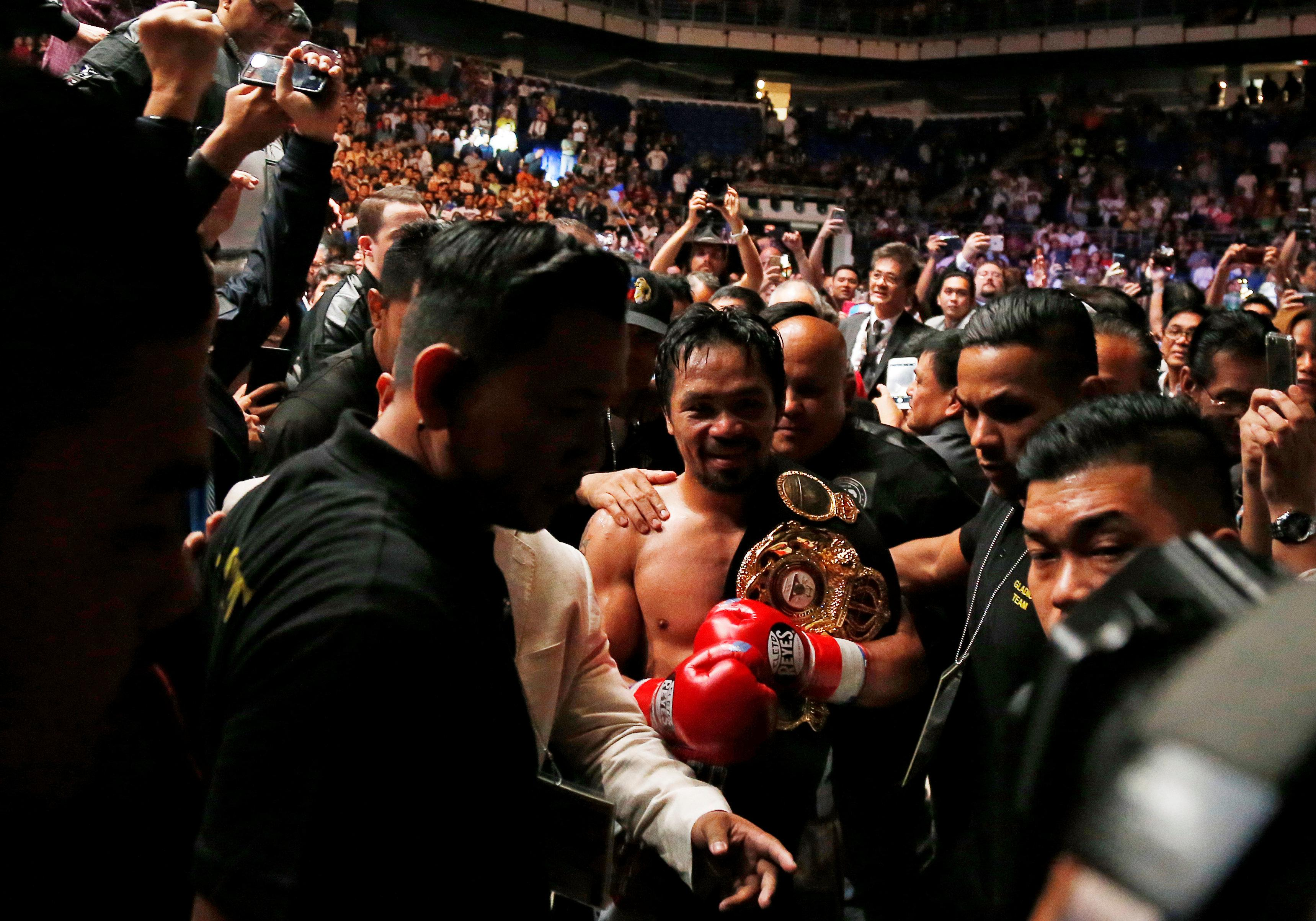 Pacquiao is mobbed by delighted fans as he departs victorious back to the dressing-room