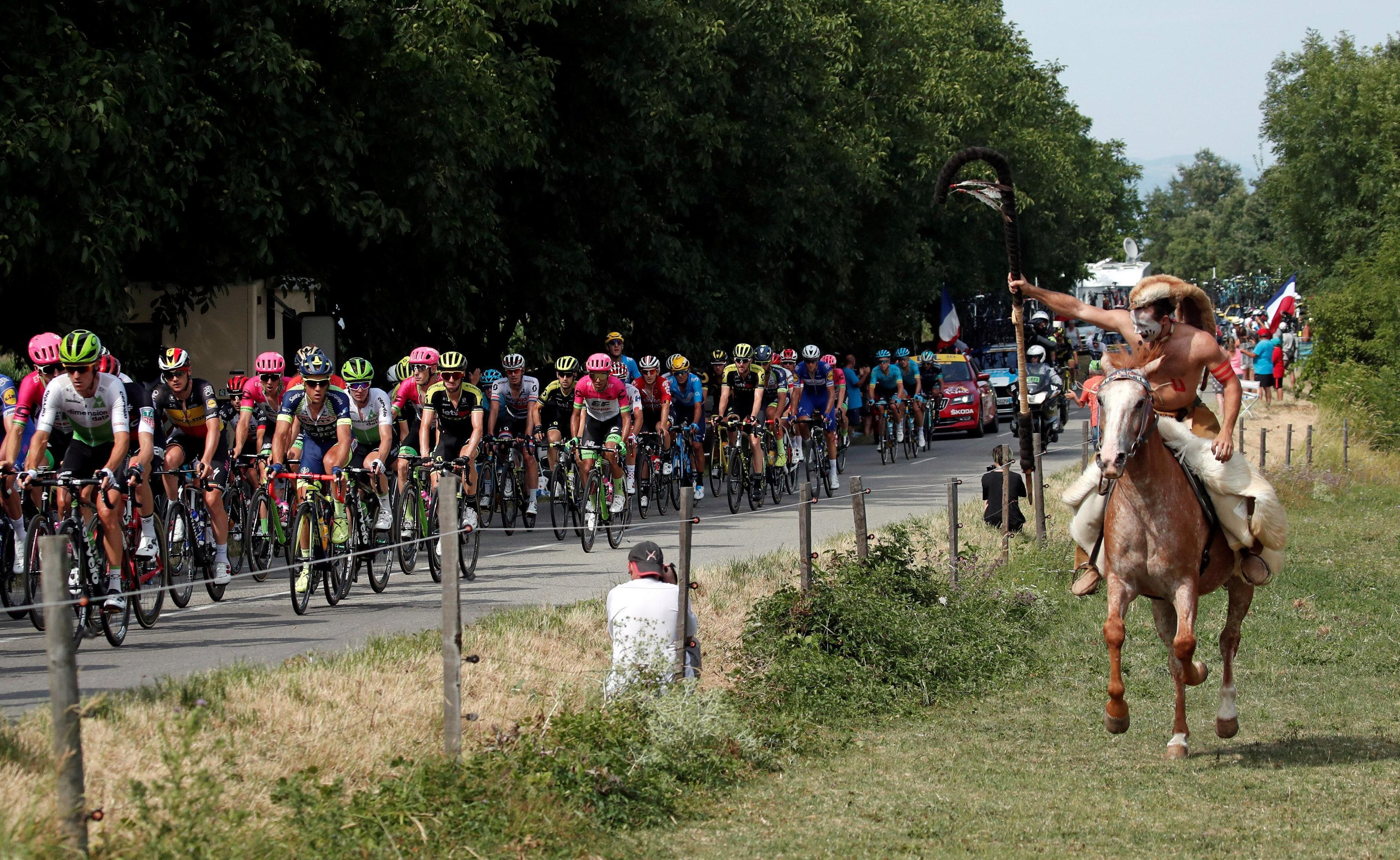 A fan on a horse cheers on the riders in a more light-hearted moment on the Tour