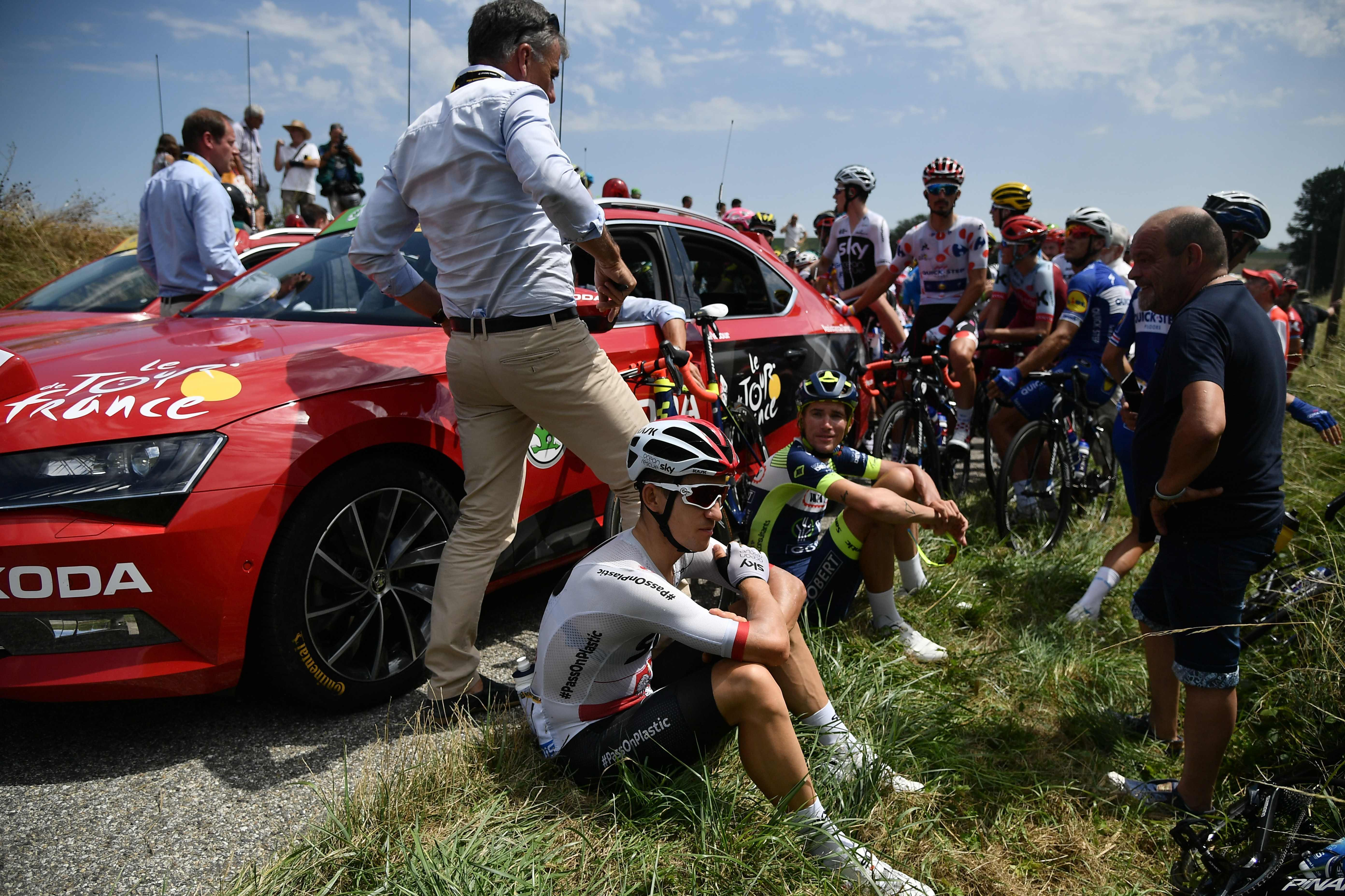 Sky rider Michal Kwiatkowski sits down on the side of the road after the incident