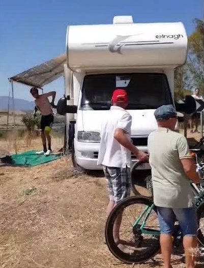 The rider emerged from the caravan with his jersey off while a fan held on to his bike