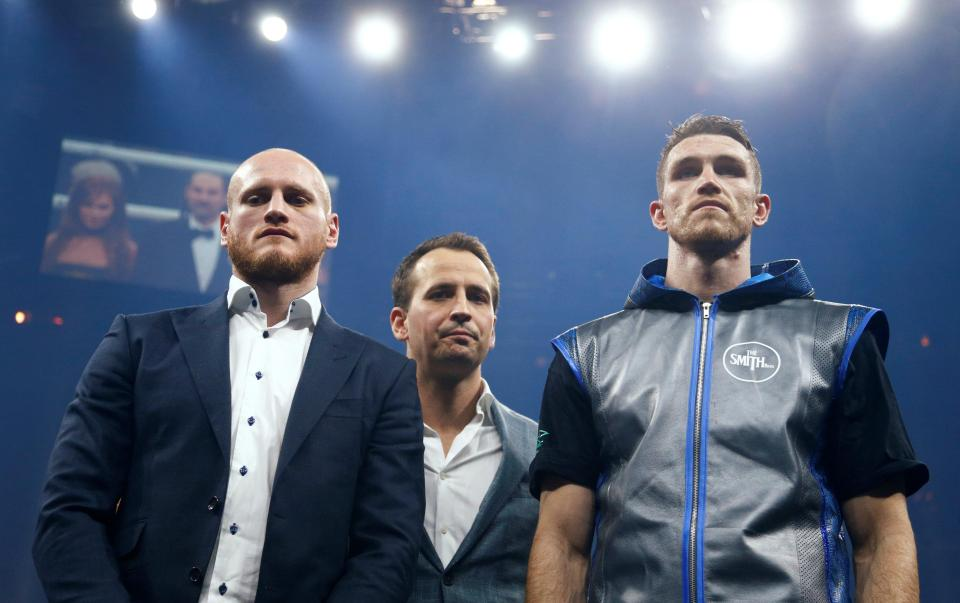 George Groves and Callum Smith face the crowd with Kalle Sauerland standing in the background under the bright lights of Nuremberg after Smith's semi-final win