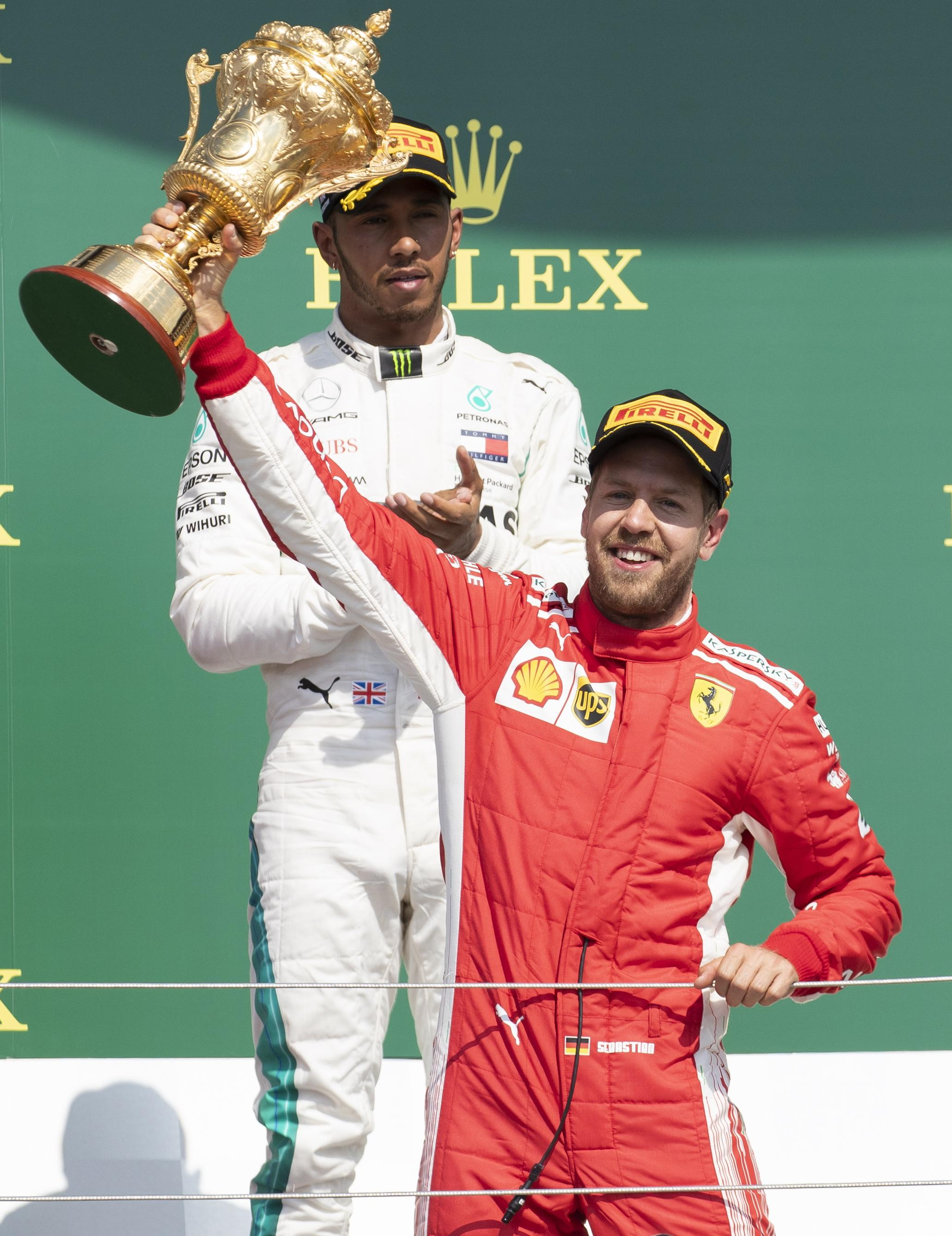Sebastian Vettel lifts the British Grand Prix trophy in July 2018, nine years after his first victory at Silverstone