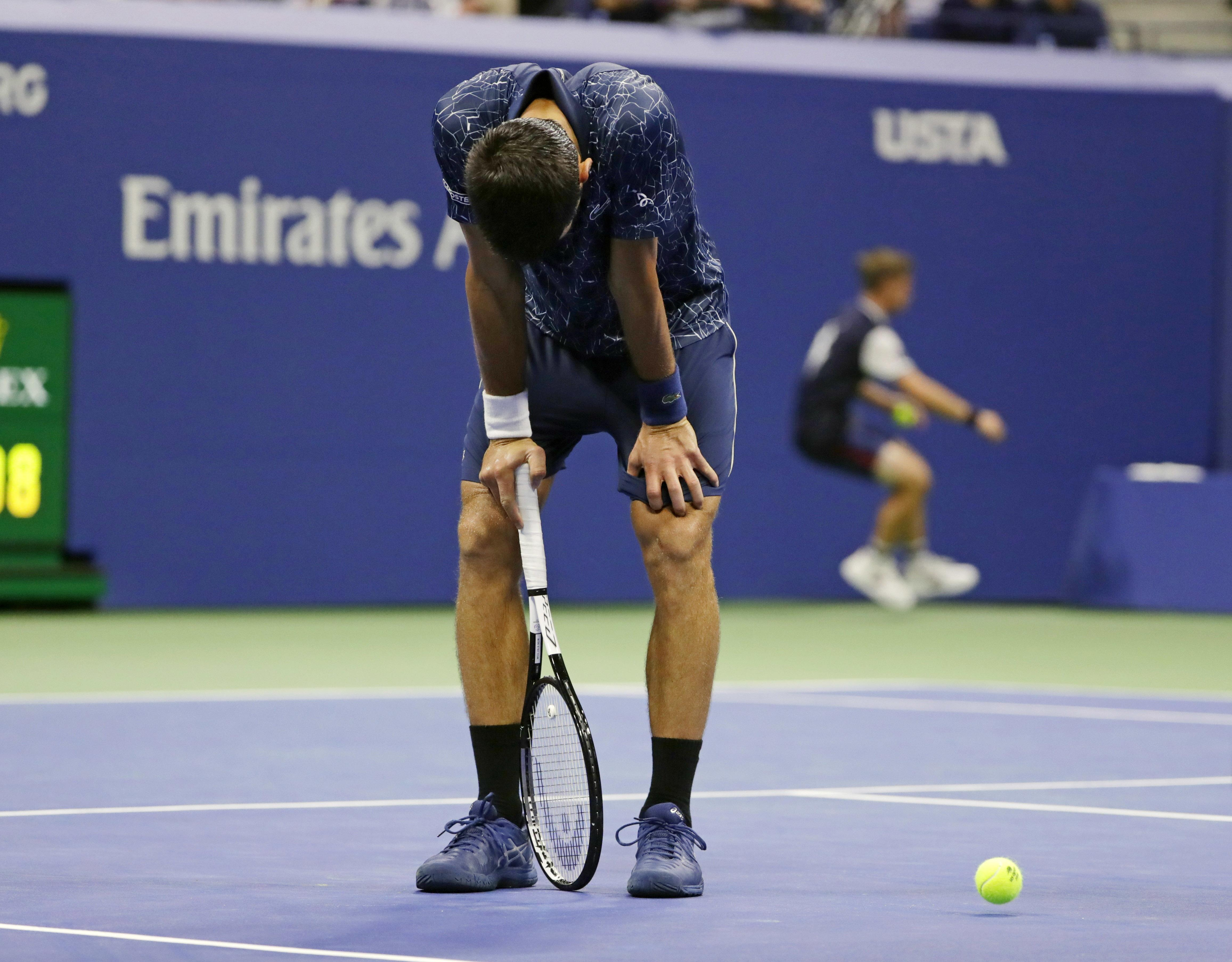 An exhausted Novak Djokovic bends over to catch his breath at the US Open