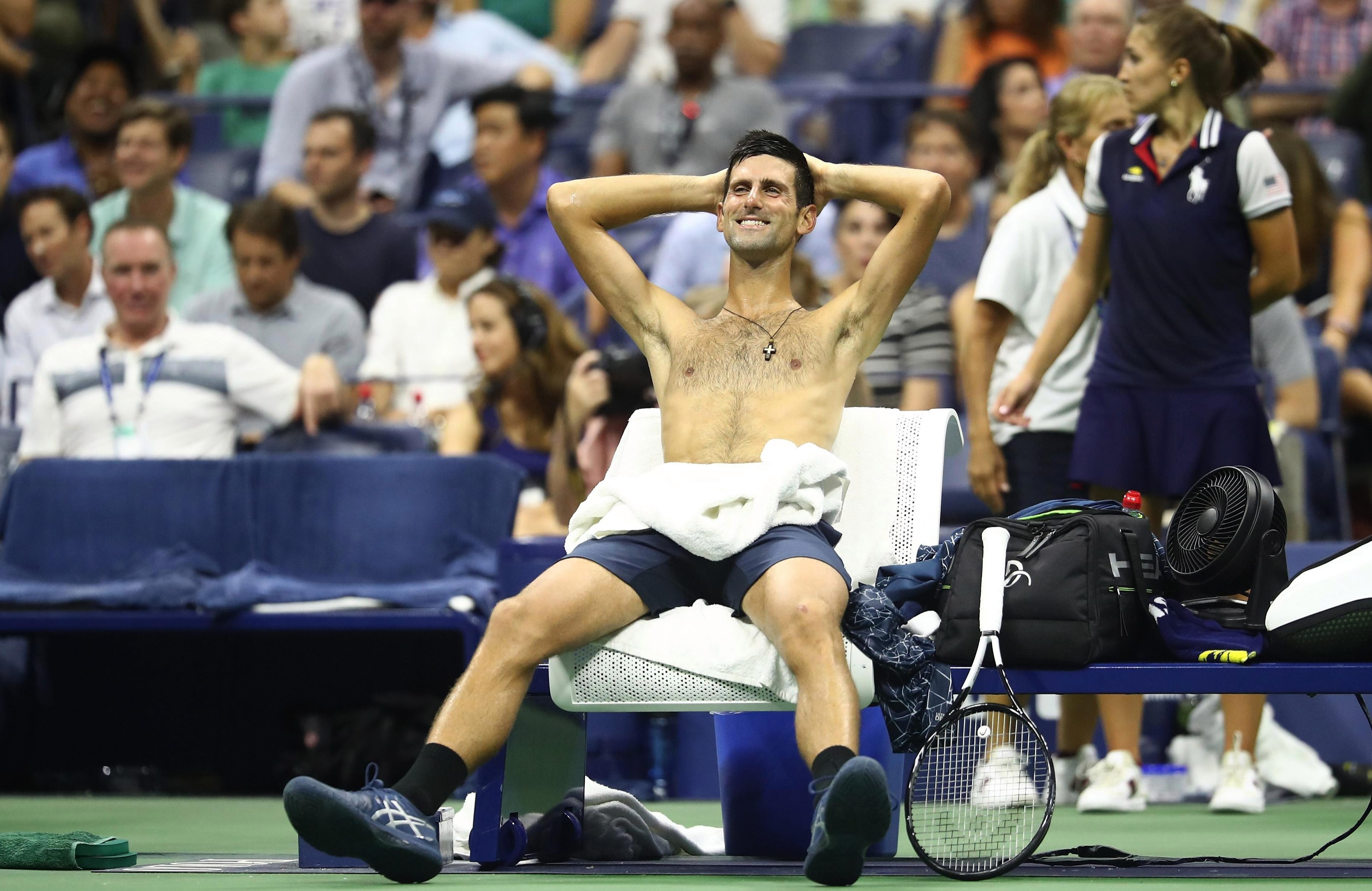 Novak Djokovic rests with his shirt off to combat the heat and humidity at Flushing Meadows