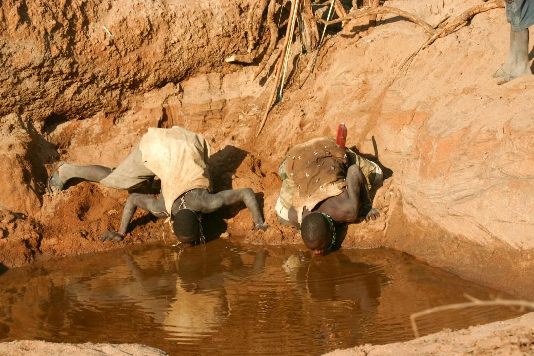 Two men drink from a muddy watering hole which has almost run dry