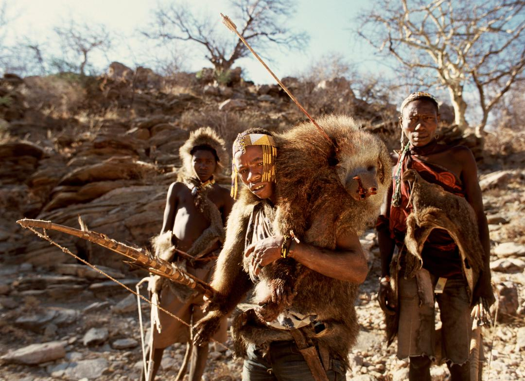 One of the tribesmen brings the head of a slain baboon back his home to be butchered