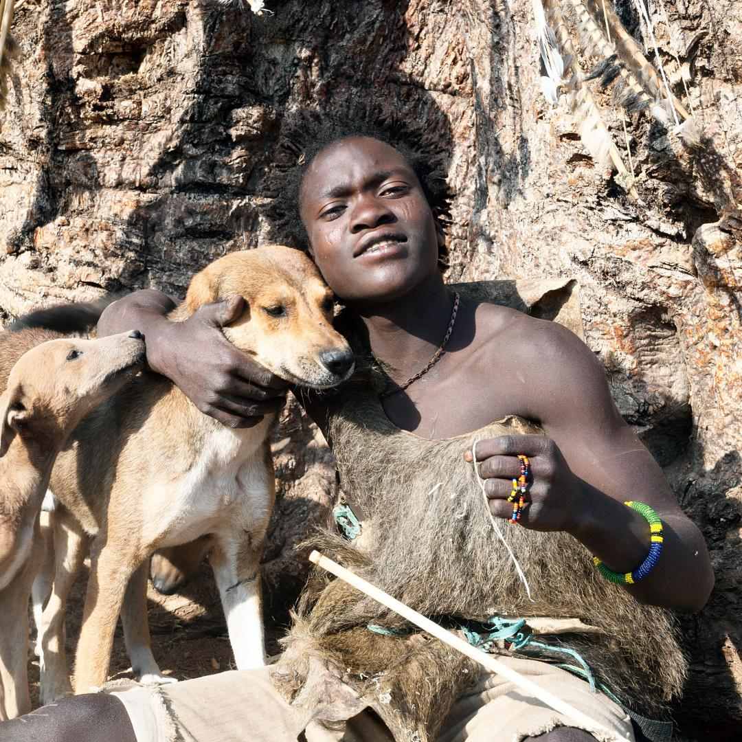 A young Hadza bushman poses with his dogs