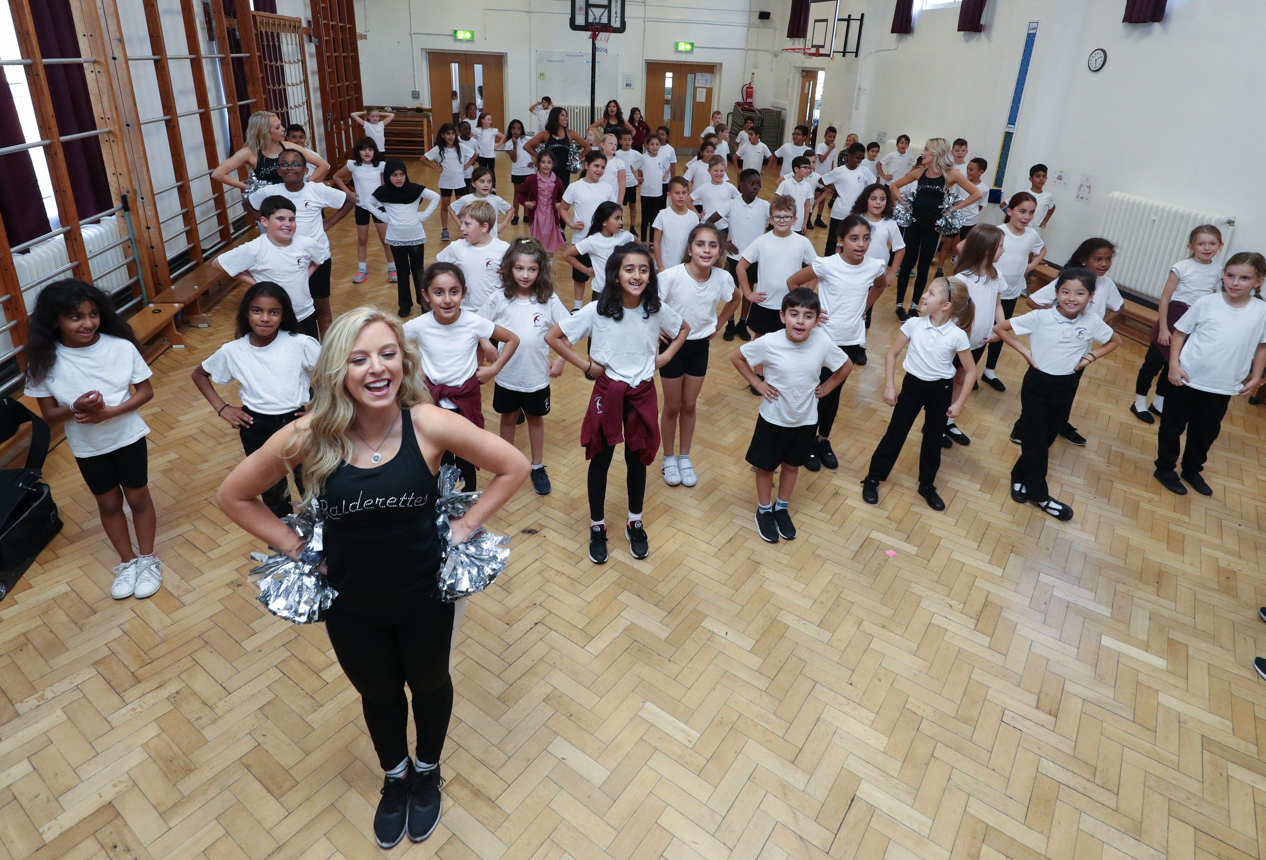 The Oakland Raiders cheerleaders teach school children their moves