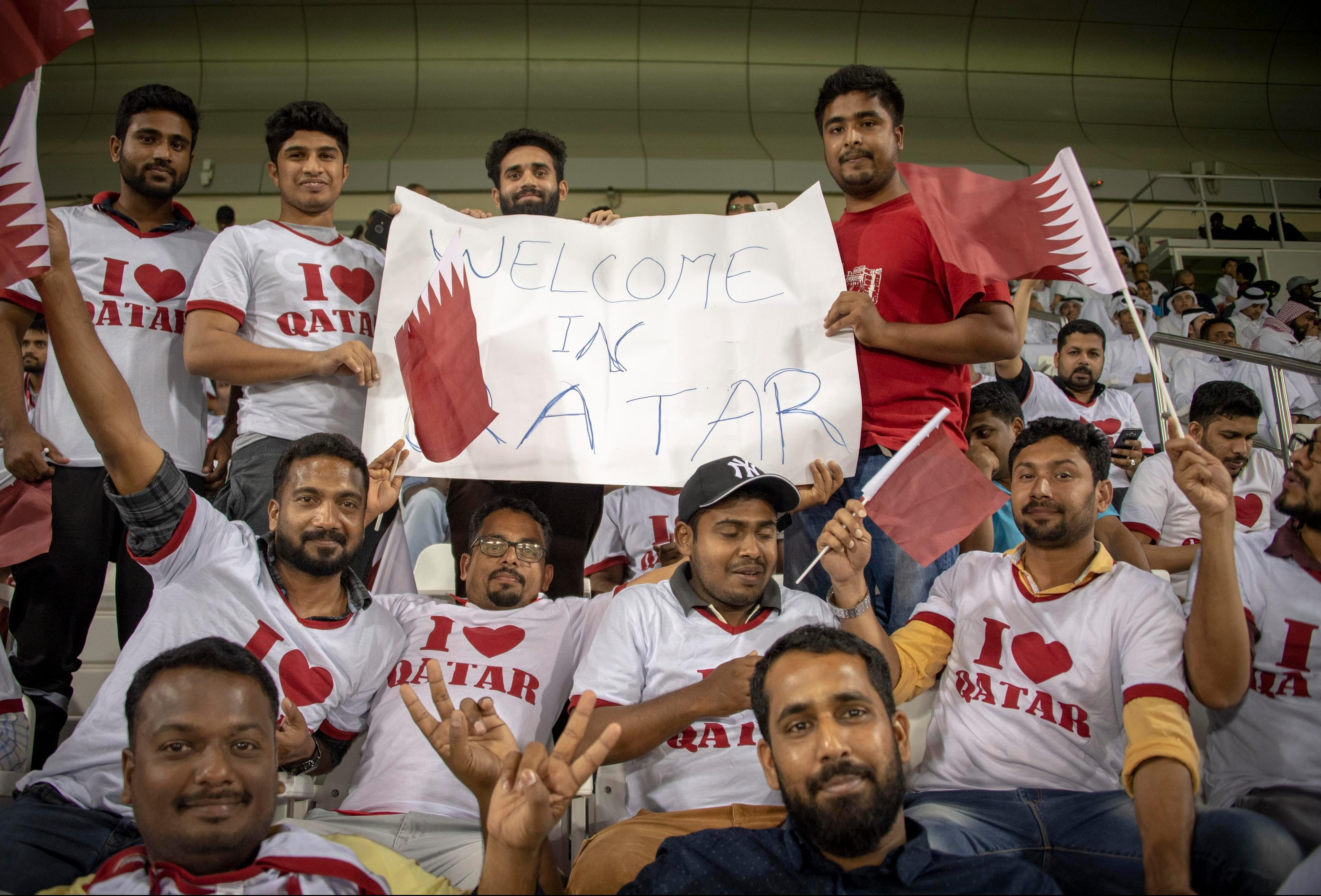 Limousine driver Jahed Mohammed, 23, right. originally from Bangladesh is part of a group holding a banner saying: Welcome in Qatar
