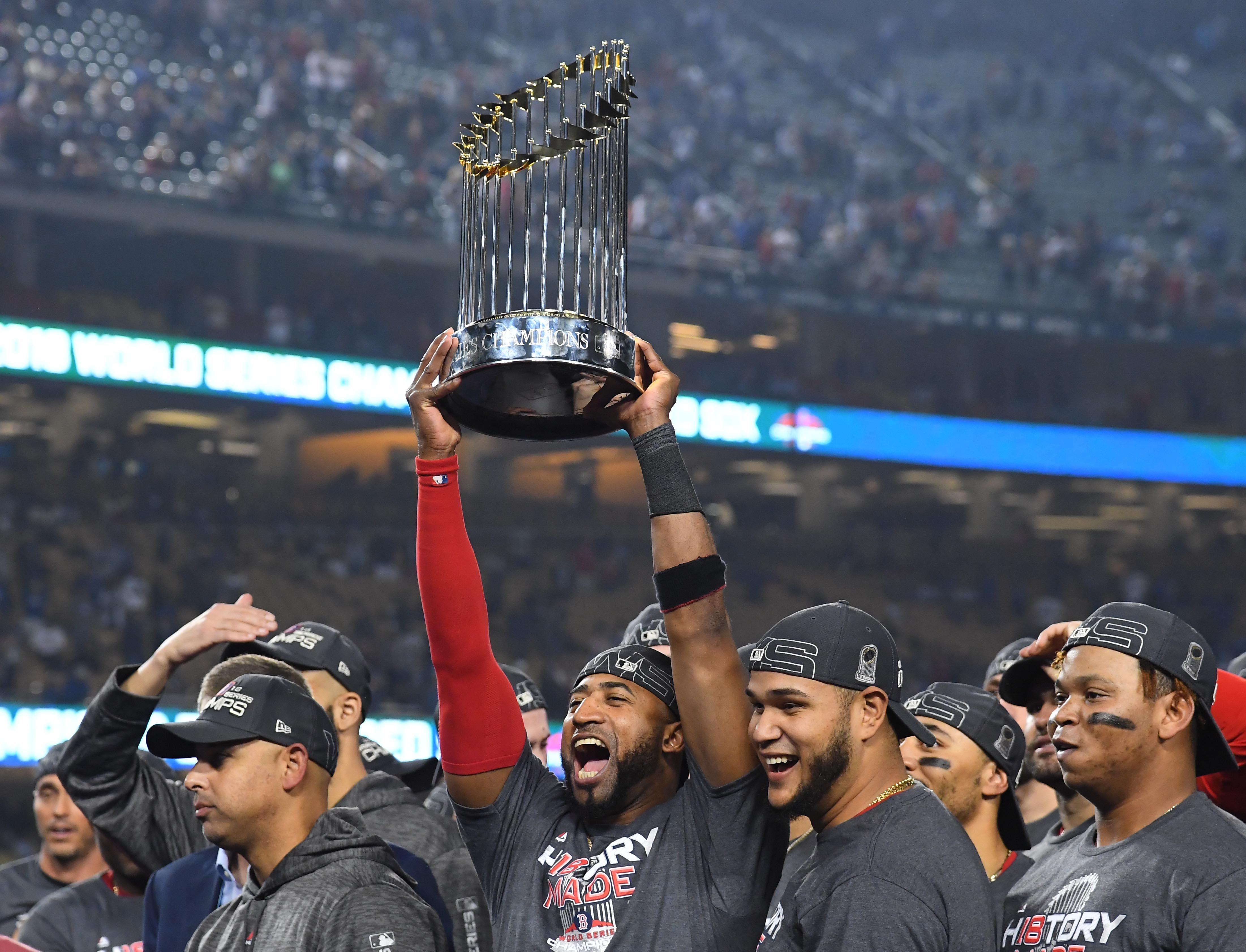 Boston Red Sox third baseman Eduardo Nunez hoists the Commissioner's Trophy after defeating the Los Angeles Dodgers