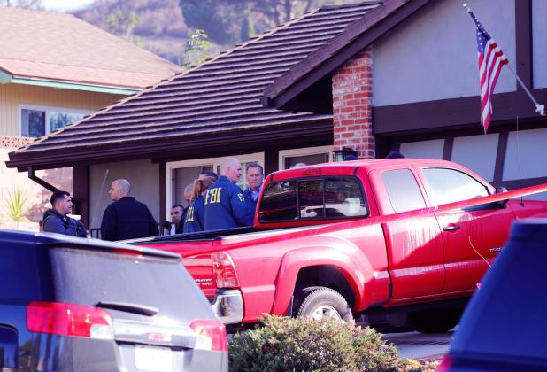 Police and FBI officers wait outside Long's house in Newbury Park which is close to the Thousand Oak Bar