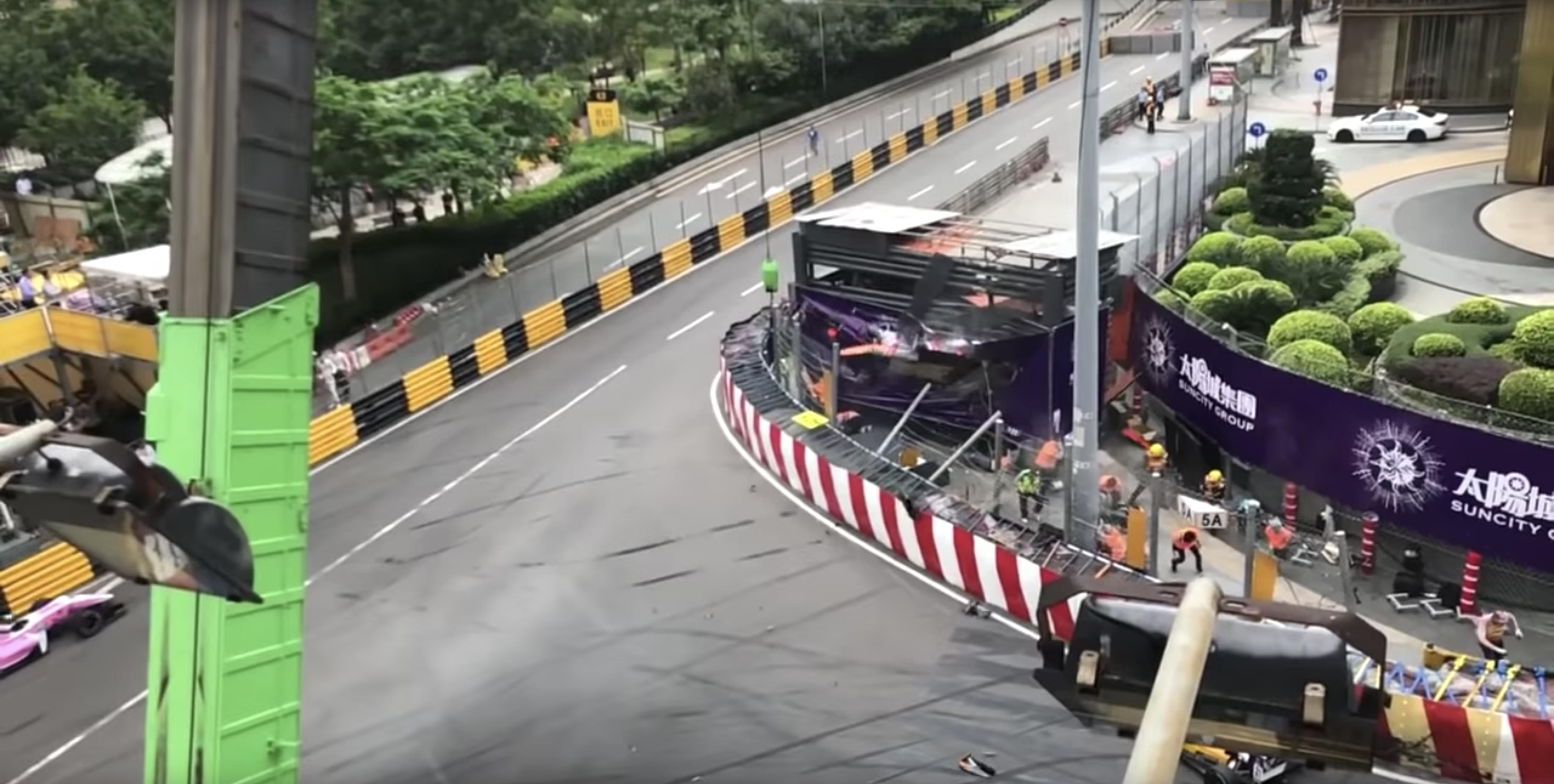 Marshals run for cover as the racing car smashes through the fencing into the stand