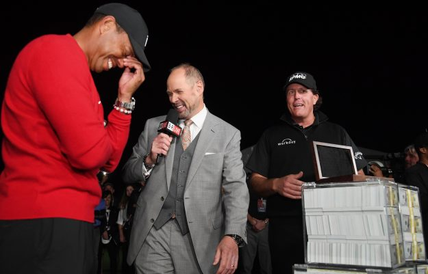 Tiger Woods laughs as Phil Mickelson collects his cash