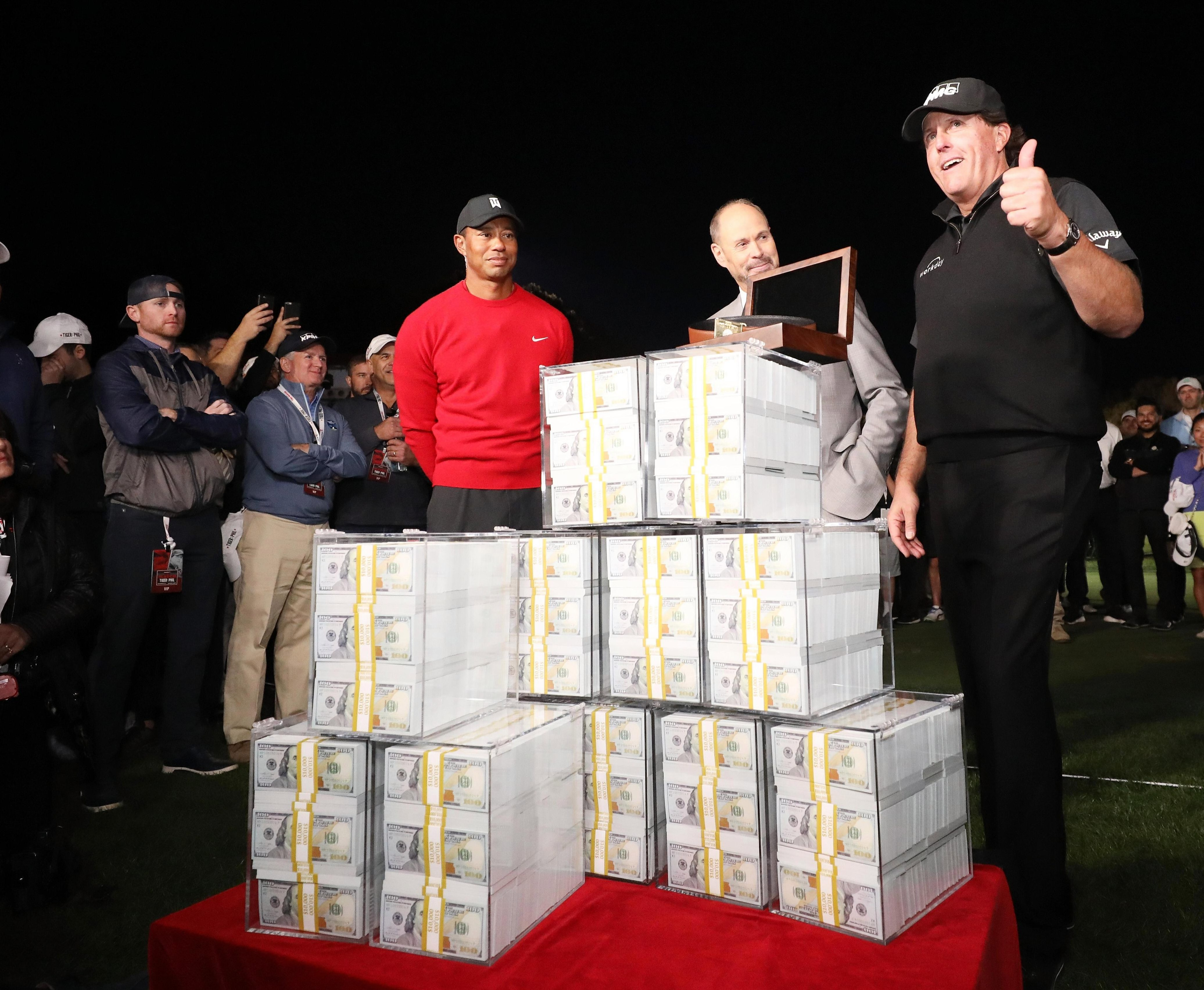 Phil Mickelson gives the thumbs up beside his $9m pile of cash
