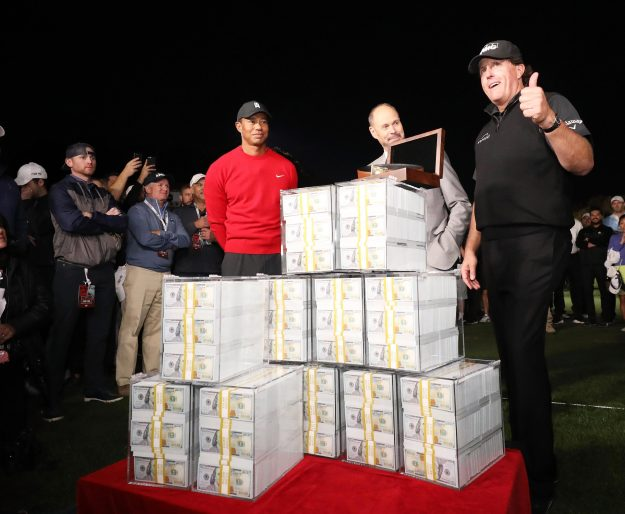 Phil Mickelson gives the thumbs up beside his m pile of cash