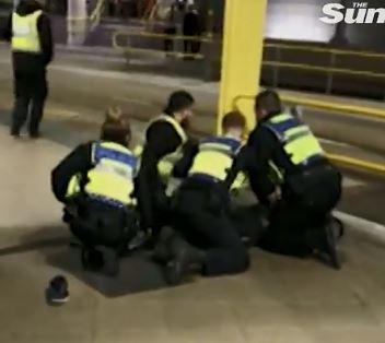 The attacker is pinned to the ground by cops after stabbing three people