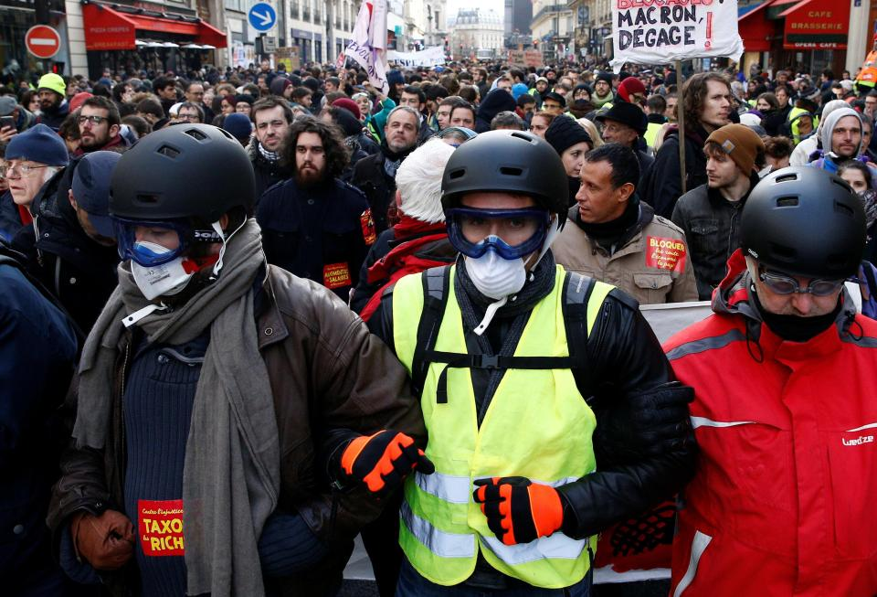 'Yellow vest' protesters link arms and wear face masks and goggles amid clashes in the capital