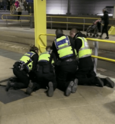 Officers restrain a suspect after three people were stabbed on New Year's Eve