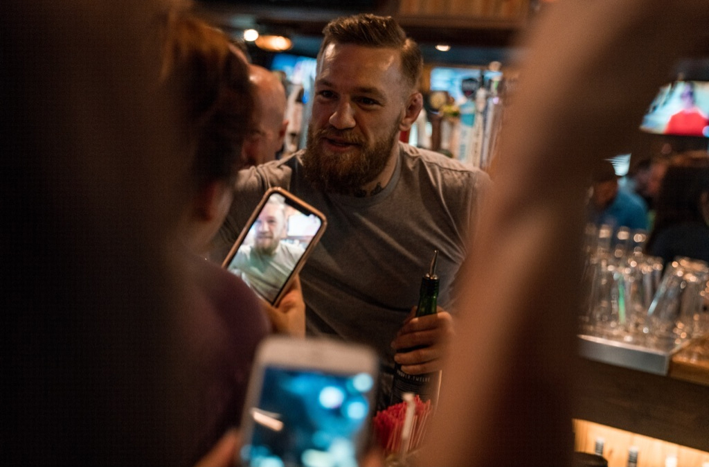 McGregor is pictured in a bar with his Proper 12 whisky in hand posing for selfies with his fans