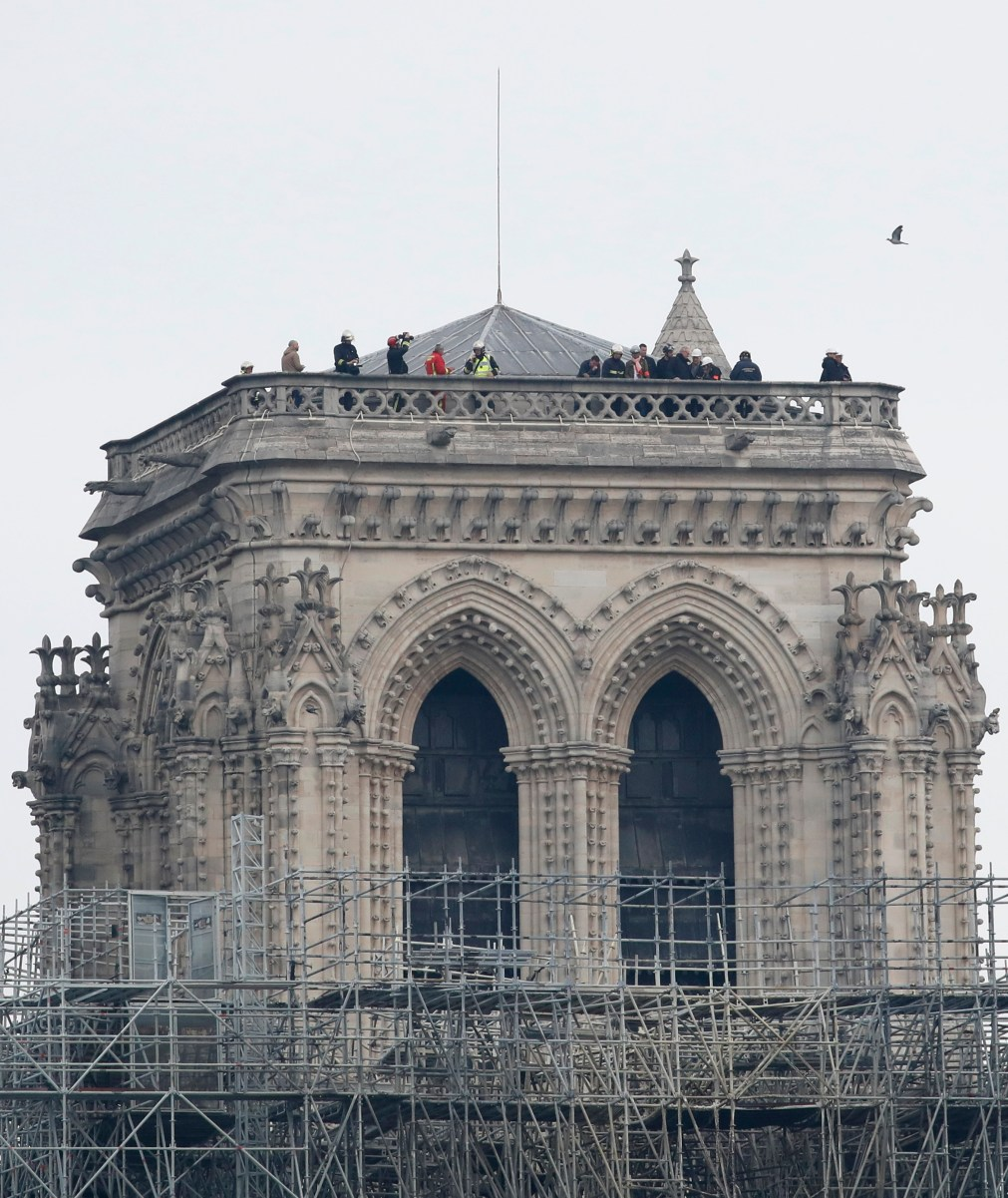 Firefighters inspect one of the two towers, which survived the blaze