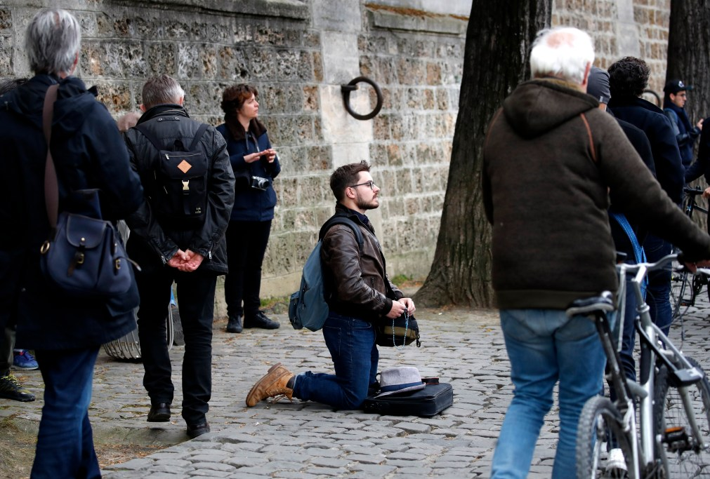 A man on his knees in prayer outside the cathedral